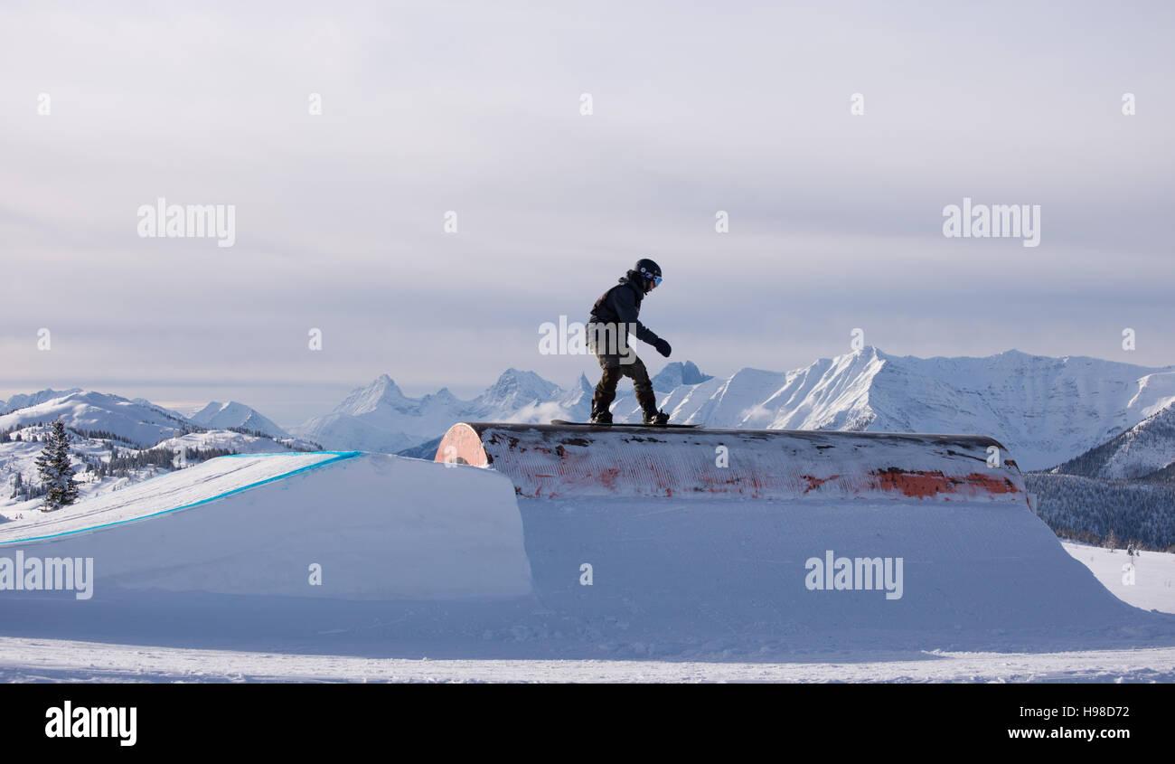 Snowboarder scorrevole una guida con le montagne sullo sfondo Immagini Stock