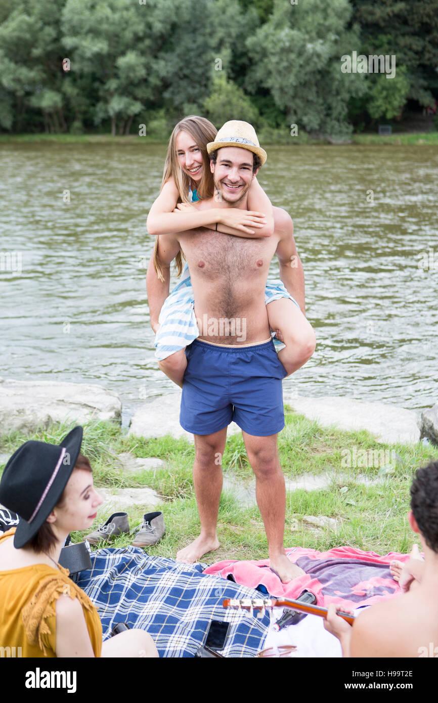 Giovane uomo dando ragazza piggyback sulla riva del fiume Immagini Stock