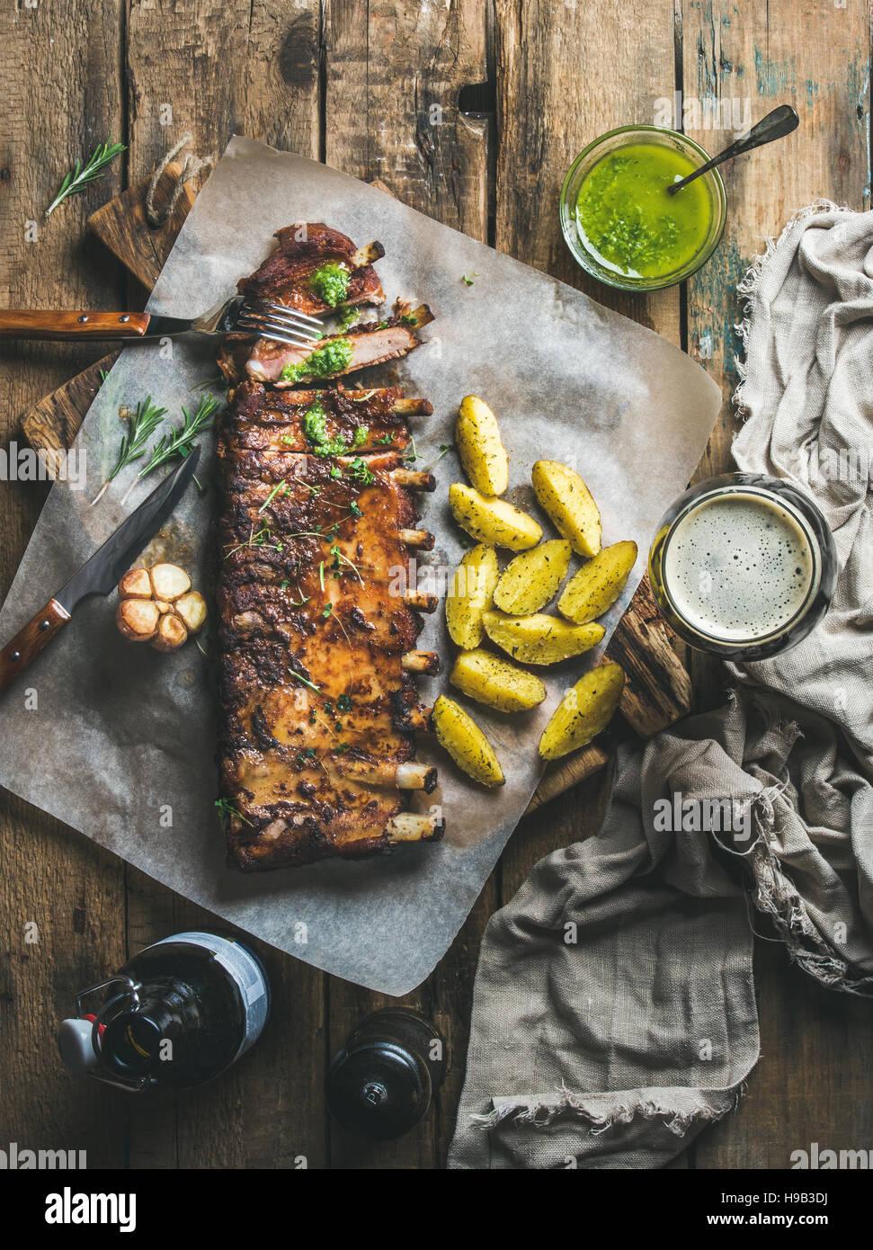 Arrosto di costolette di maiale alle spezie con patate fritte e birra scura Immagini Stock
