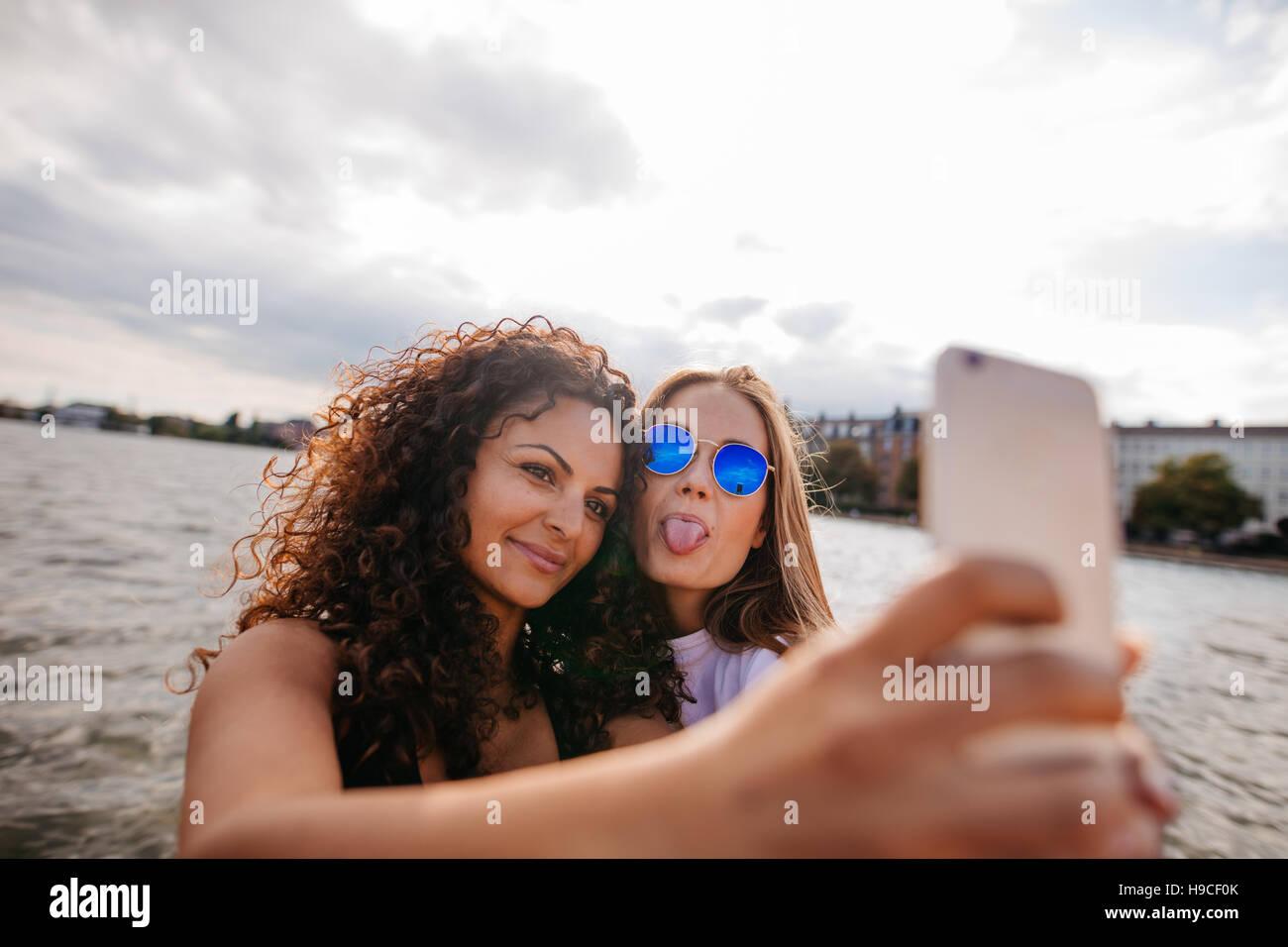 Colpo di ragazze adolescenti tenendo selfie con smart phone dal lago. Uno spuntavano lingua con altra azienda telefono Immagini Stock