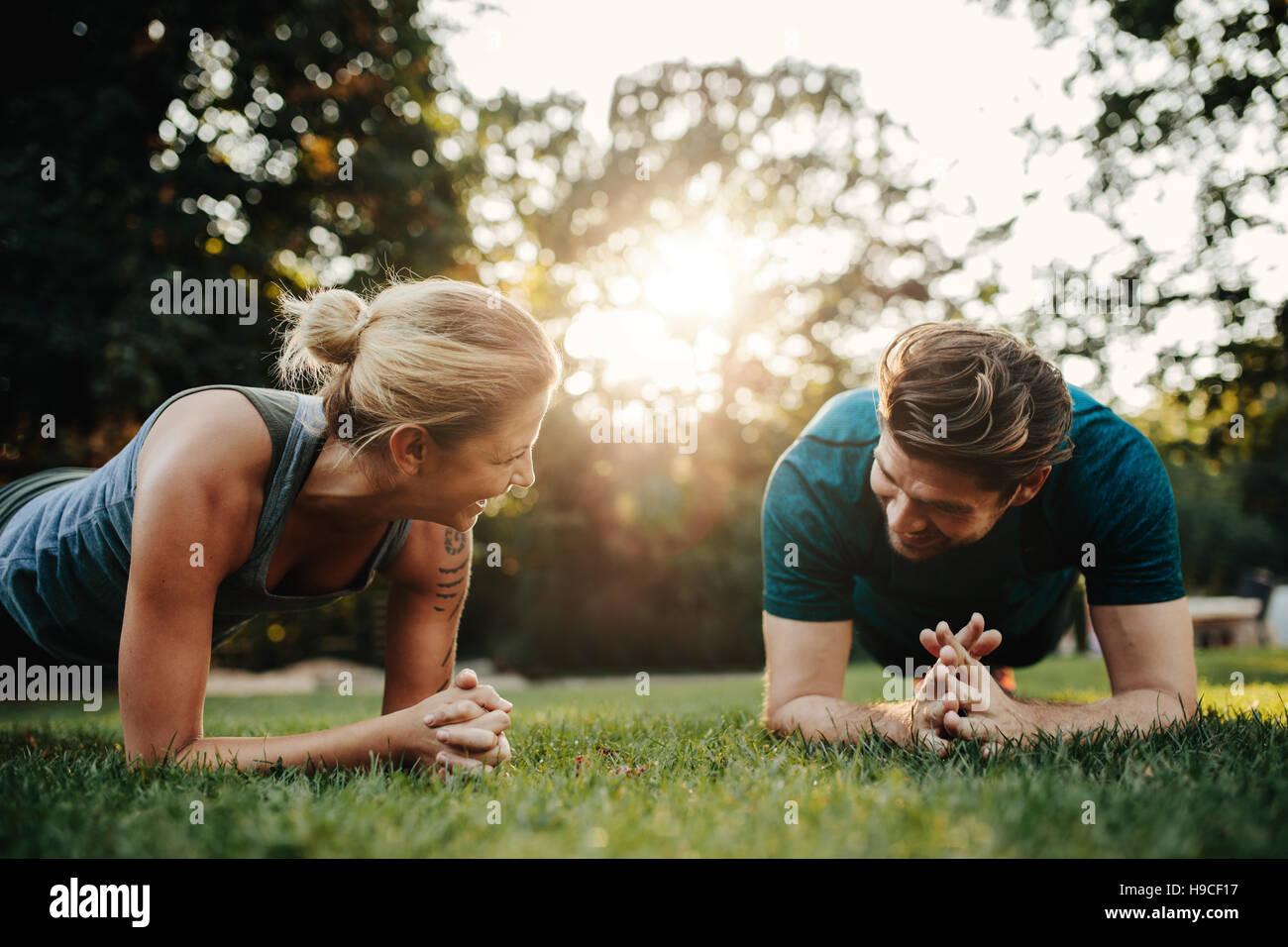 Coppia caucasica facendo allenamento core insieme nel parco. Montare il giovane uomo e donna che esercitano. Immagini Stock