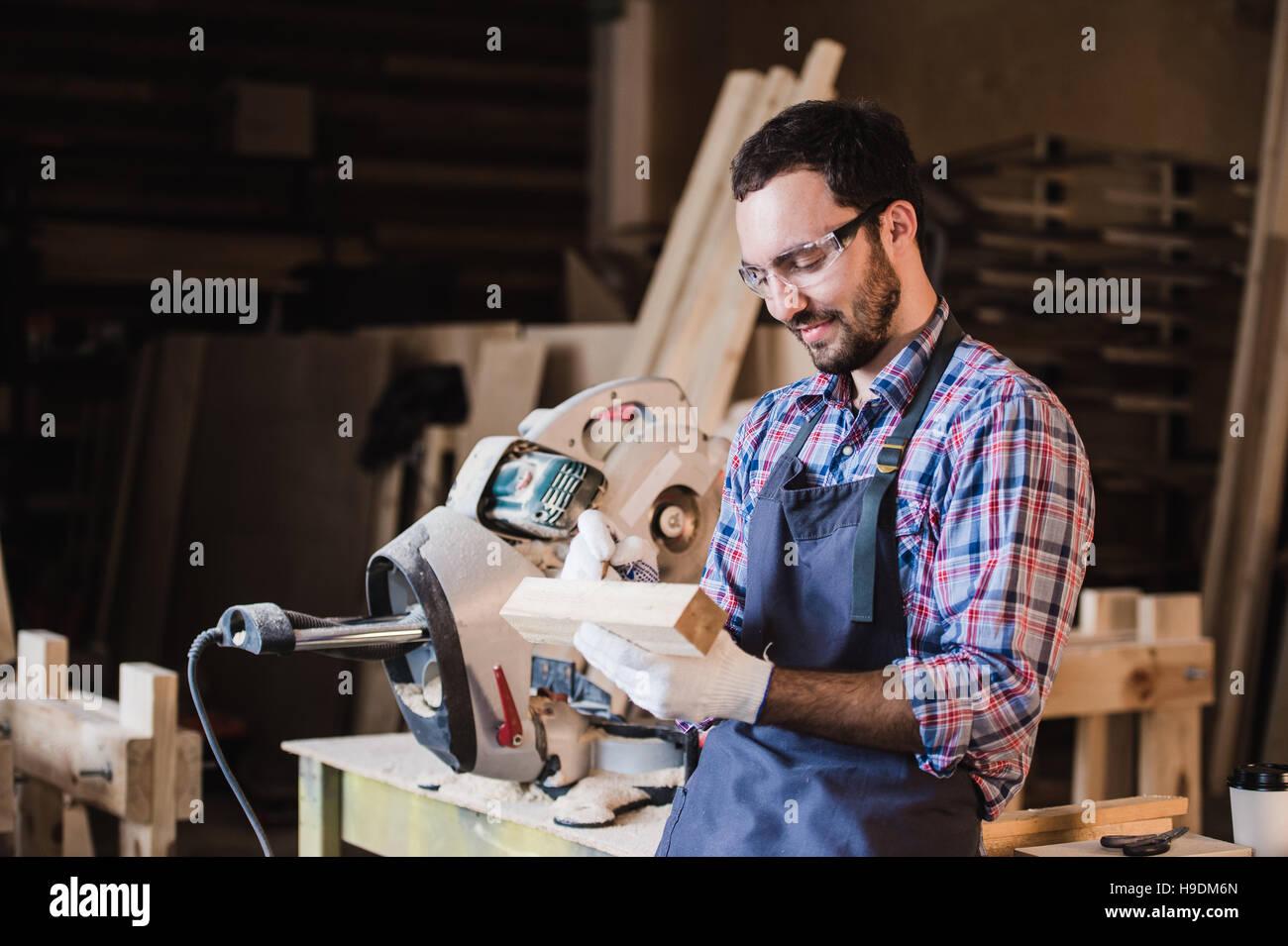 Bello il carpentiere in occhiali protettivi è guardando la fotocamera e sorridere mentre in piedi vicino al Immagini Stock