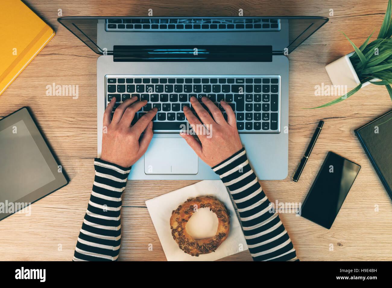 Ufficio quotidiana vita, mani femminili lavorando sul computer portatile - vista superiore di imprenditrice tastiera Immagini Stock