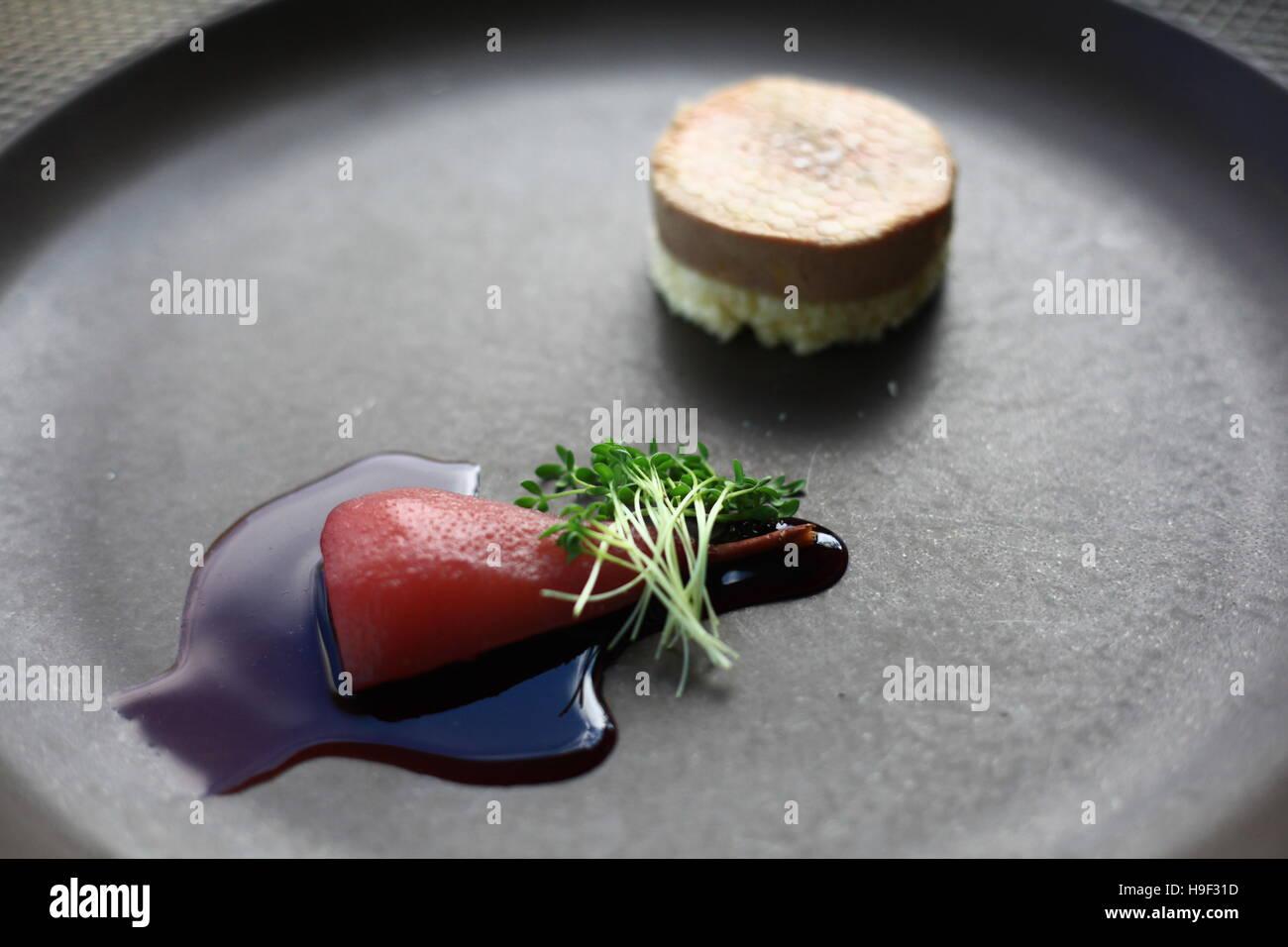 Il Foie gras torchon con brioche, pera affogata in salsa di vino rosso Immagini Stock