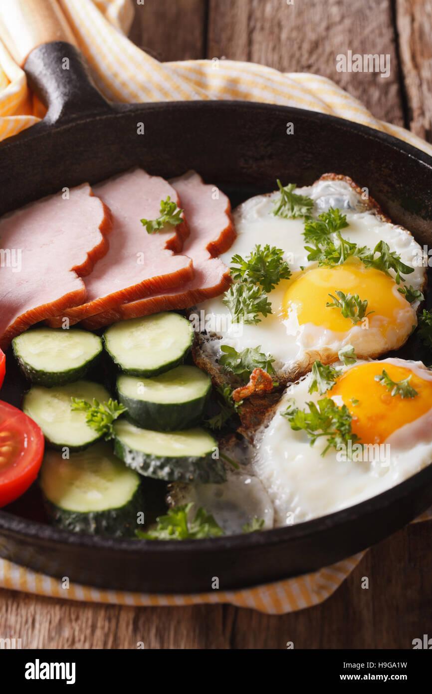 Colazione casalinga: uova fritte con prosciutto e verdure fresche in una padella di close-up verticale. Immagini Stock