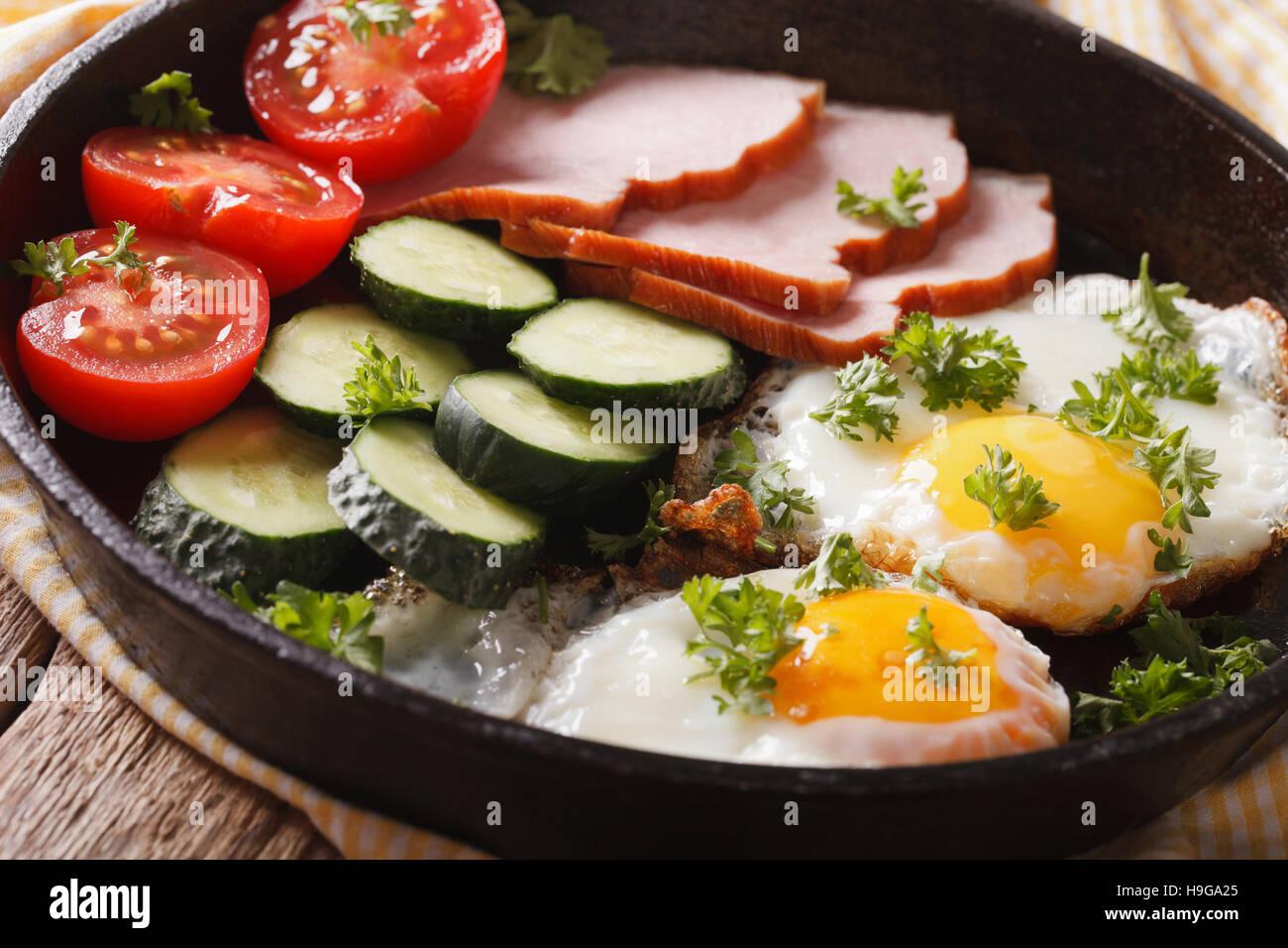 Colazione casalinga: uova fritte con prosciutto e verdure fresche in una padella di close-up. Posizione orizzontale Immagini Stock