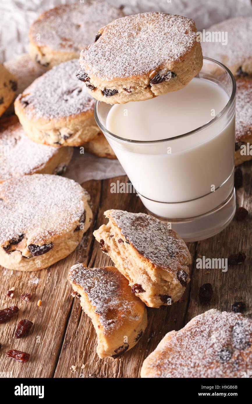 Deliziose torte gallesi con uvetta e latte sul tavolo di close-up verticale. Immagini Stock