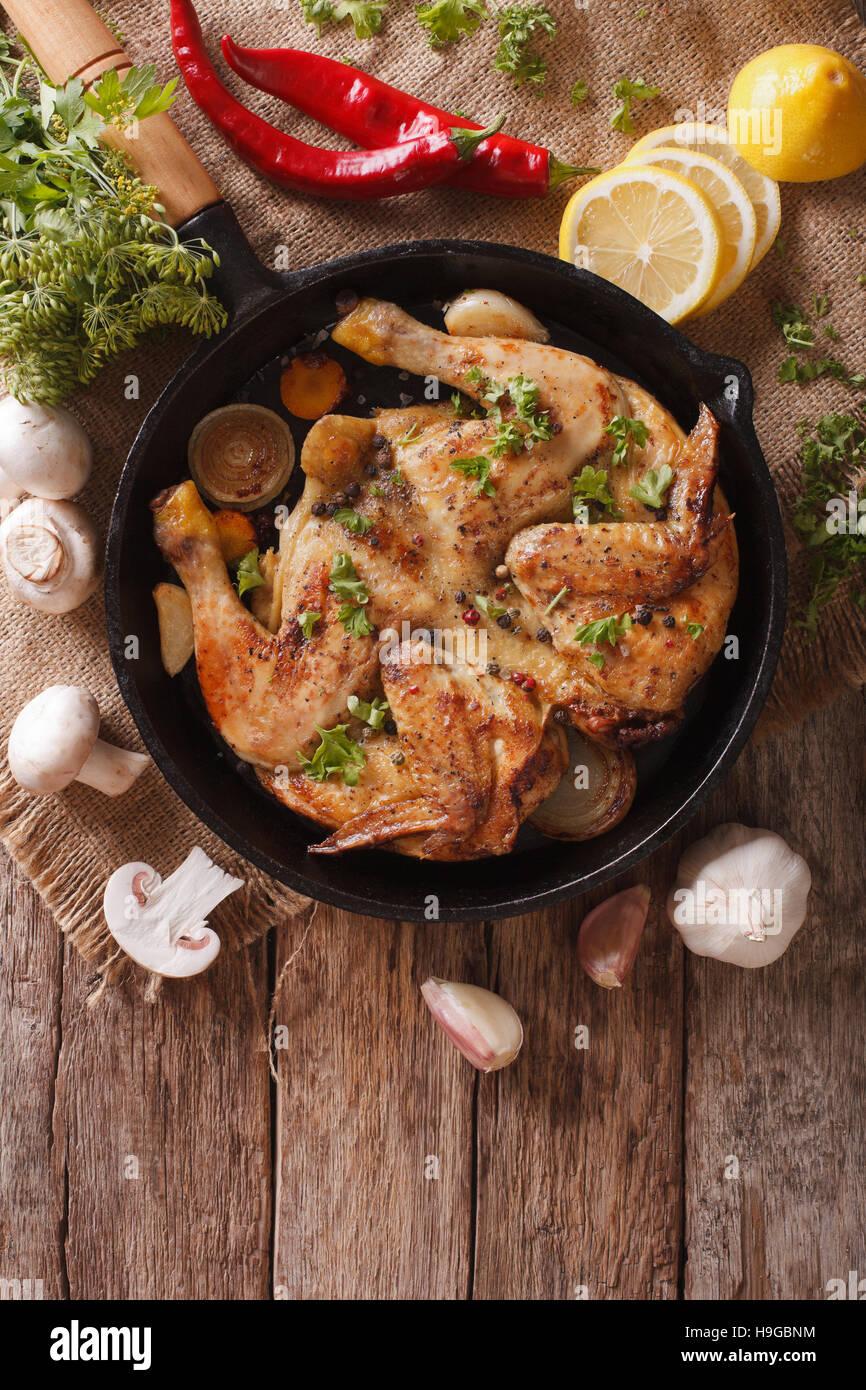 Hot fritto di pollo tabacco con erbe e aglio in una padella di close-up. Vista verticale da sopra Foto Stock
