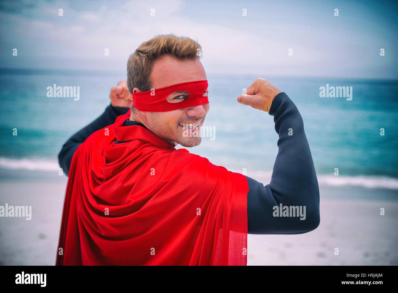 Uomo in costume da supereroe flettendo muscoli alla riva del mare Immagini Stock
