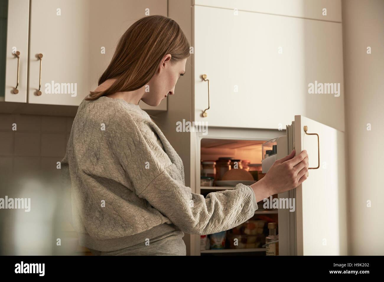 Donna che guarda in frigo Immagini Stock