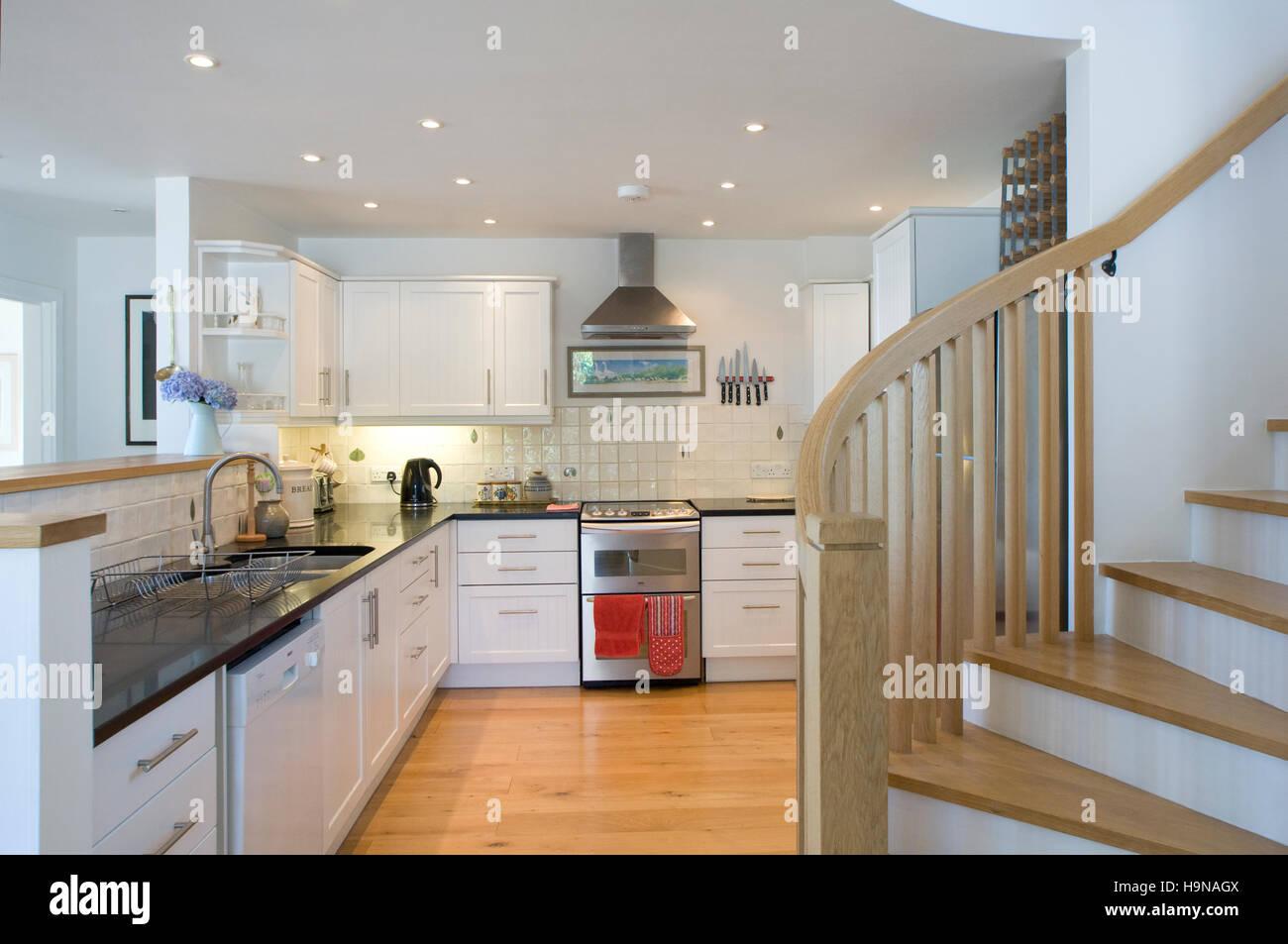 Cucina contemporanea con scalinata, luminoso, pulito, nuovo, finitura bianca. Immagini Stock