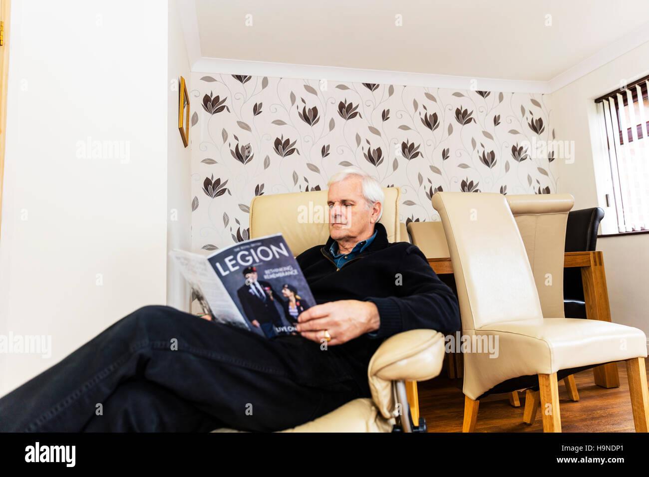 OAP lettura British Legion magazine uomo lettura sedette rilassante guardando magazine a casa REGNO UNITO Inghilterra Immagini Stock