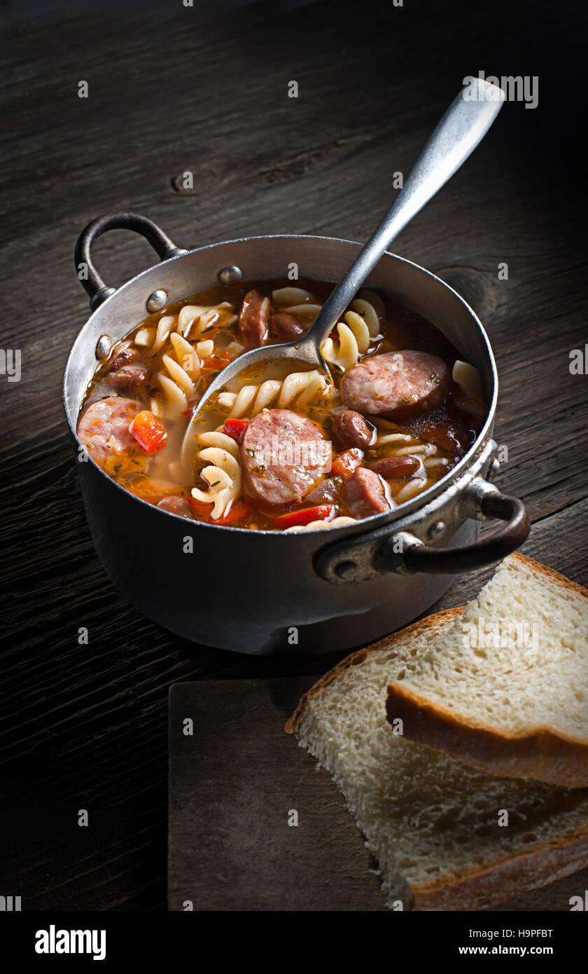 Stufato di caldo con salsiccia, i fagioli e la pasta su sfondo di legno Immagini Stock