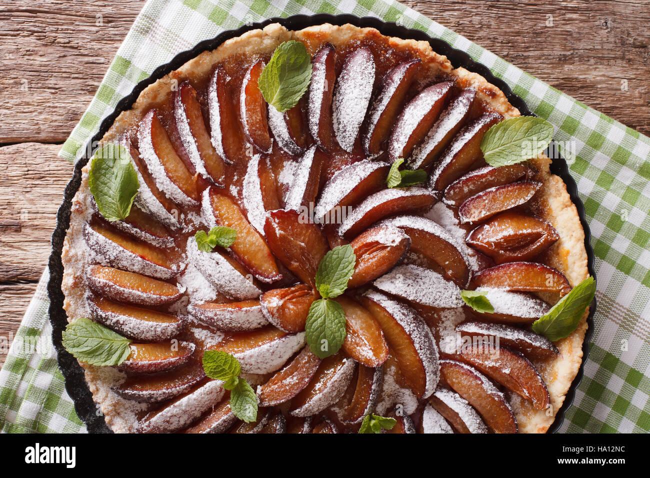Deliziosi dolci: prugna crostata con menta e zucchero in polvere vicino sul tavolo. Vista orizzontale dal di sopra Immagini Stock