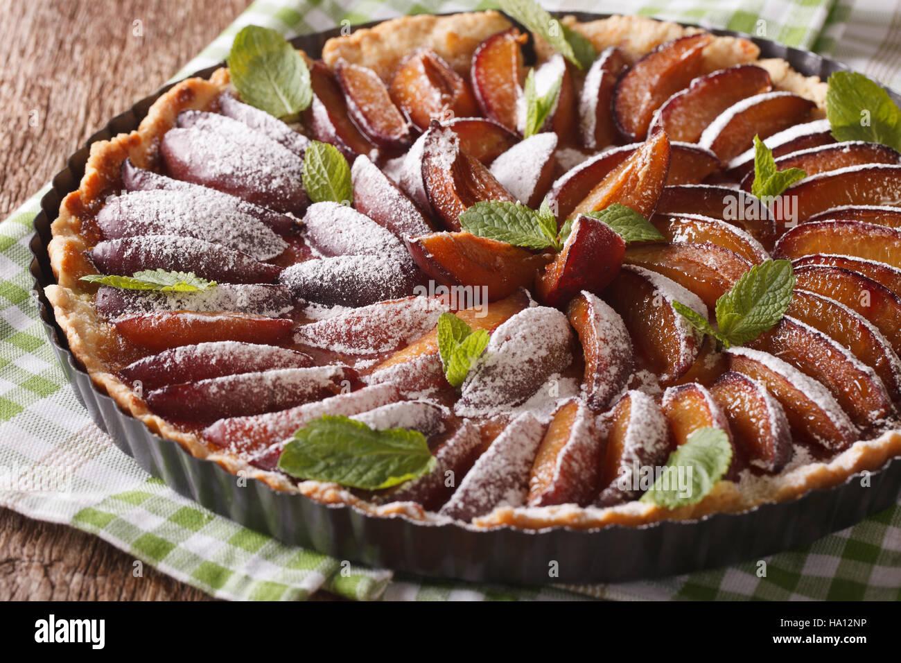 Deliziosi dolci: prugna crostata con menta e zucchero in polvere vicino sul tavolo orizzontale. Immagini Stock