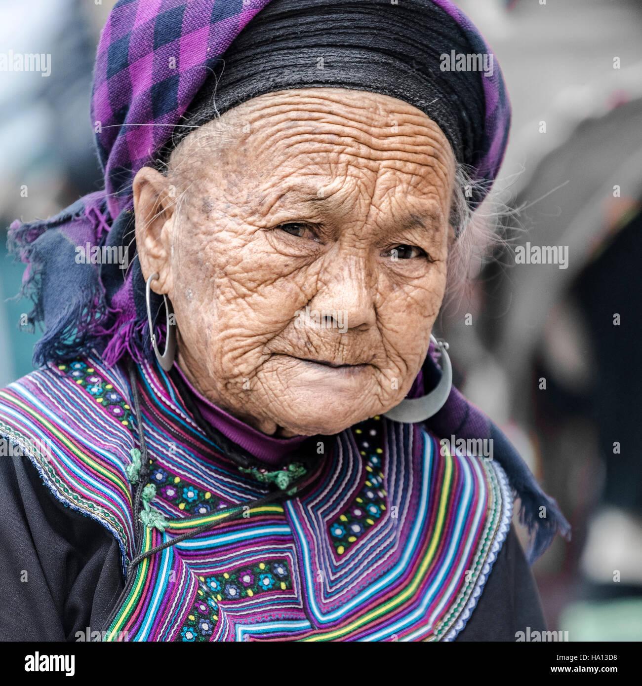 Nero donna Hmong in attesa per i clienti sul mercato locale di Sapa, il Vietnam Asia Immagini Stock