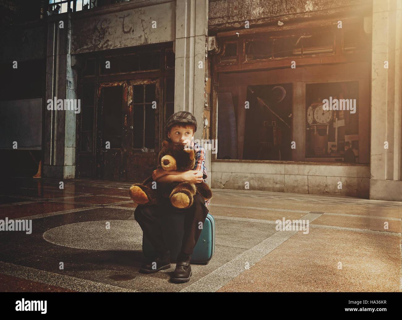 Paura di un giovane ragazzo che è seduto su una valigia di viaggio in un vecchio edificio tenendo un orsacchiotto Immagini Stock