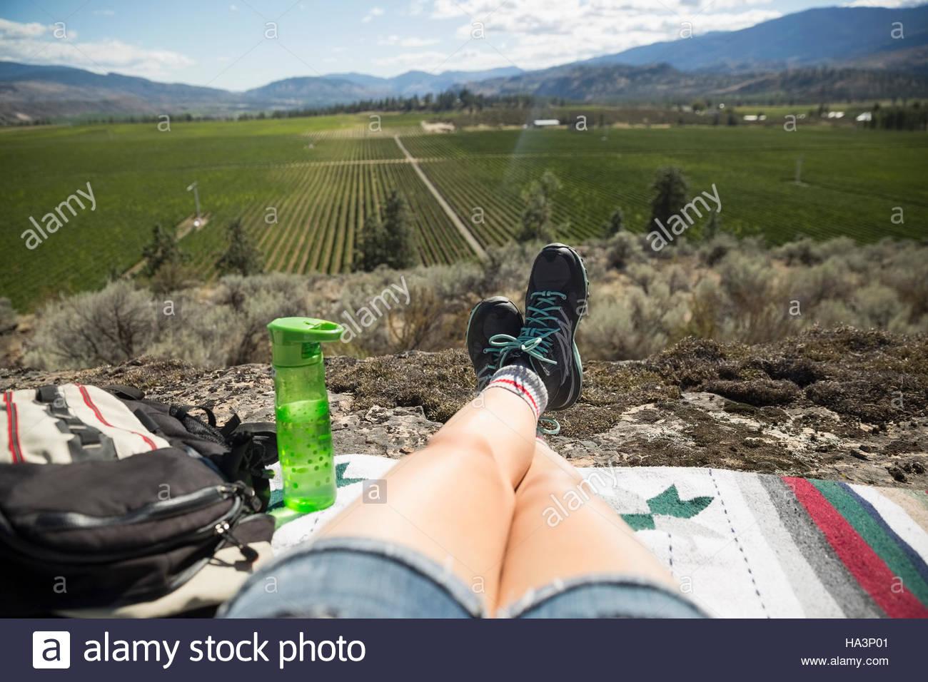 Punto di vista personale donna escursionista rilassante guardando soleggiata vista rurale Immagini Stock
