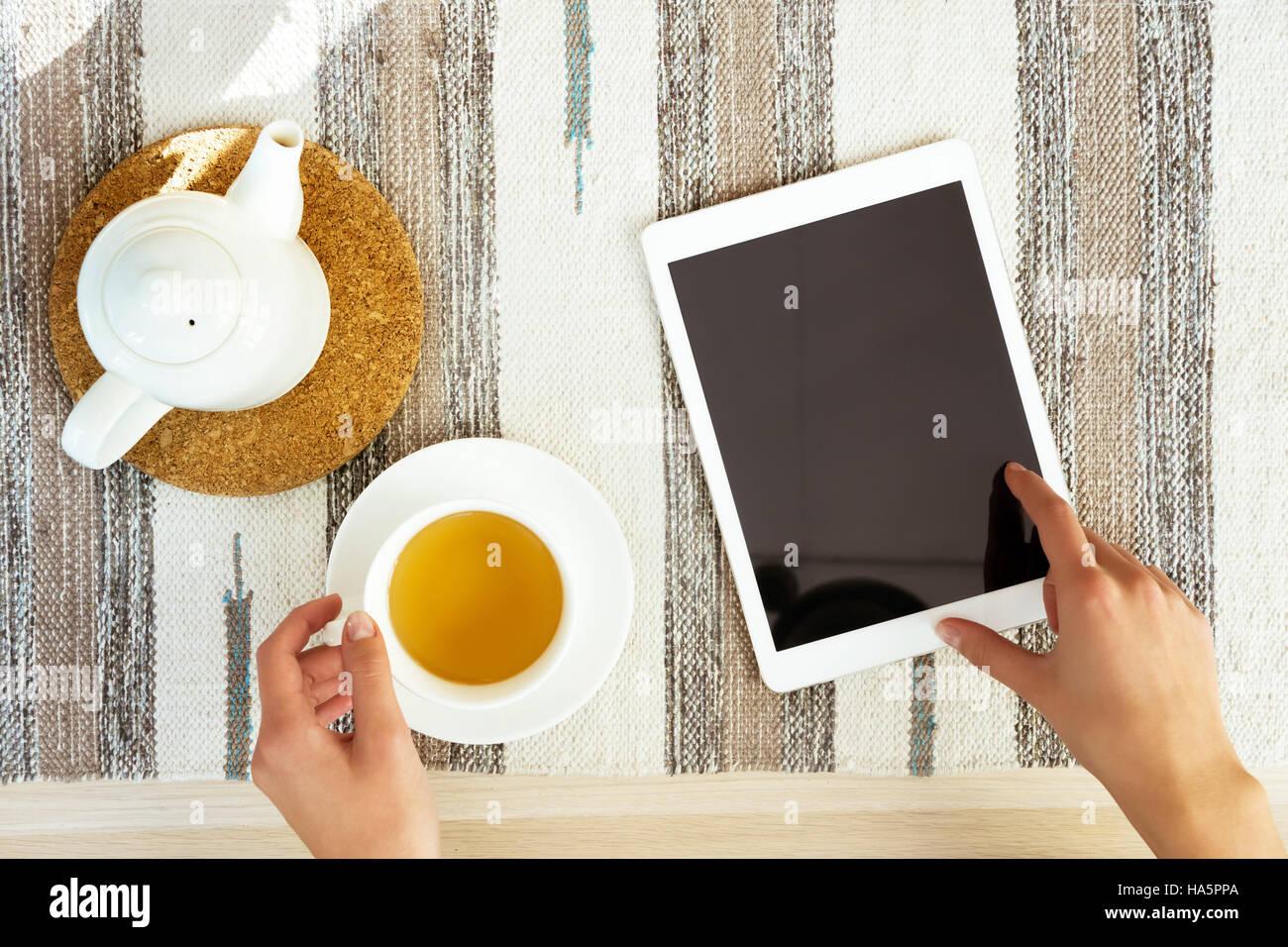 Impostare le mani computer tablet tazza da tè tabella Immagini Stock