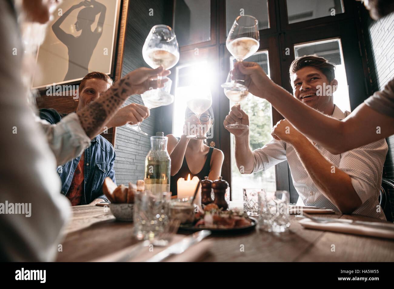 Gruppo di giovani di fare un brindisi al ristorante. Gli uomini e le donne sedute a un tavolo in cafe e tostatura Immagini Stock