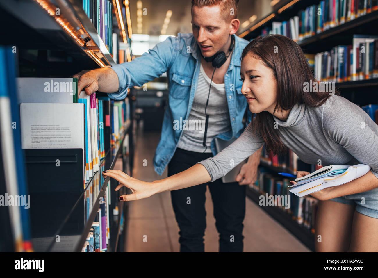 I giovani studenti di trovare libri di riferimento nella biblioteca universitaria. L uomo e la donna come trovare Immagini Stock