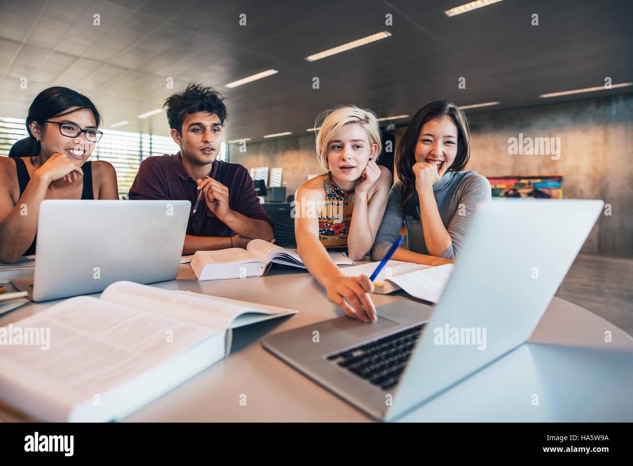 Gli studenti universitari utilizzando computer portatile mentre è seduto al tavolo. Gruppo di studio per la Immagini Stock