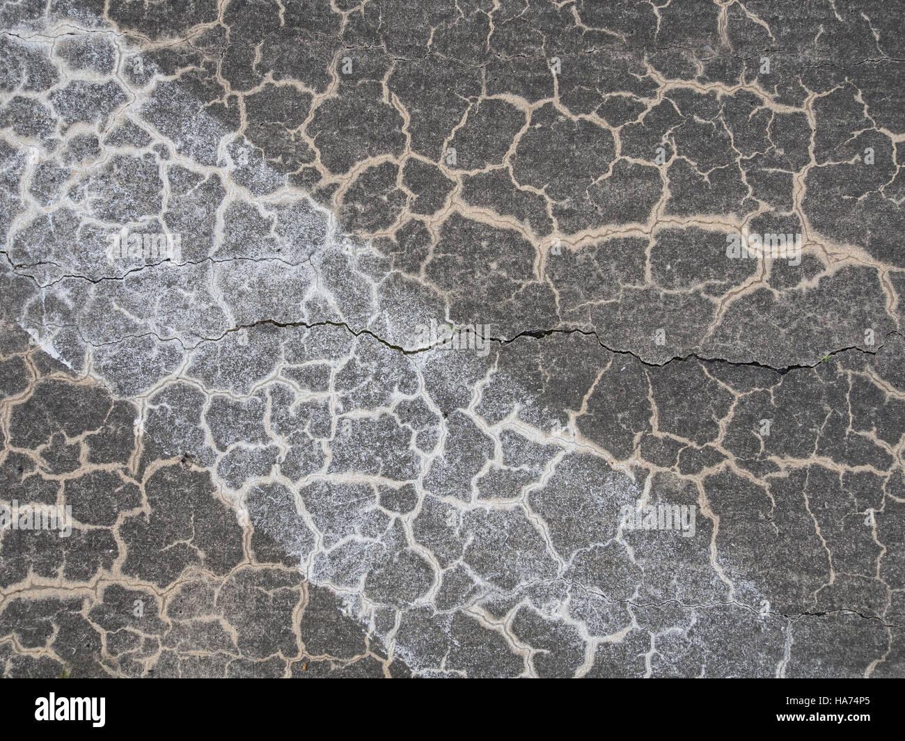 Superficie strutturata di un weathered, incrinato grigio pavimentazione in calcestruzzo con striscia diagonale di Immagini Stock
