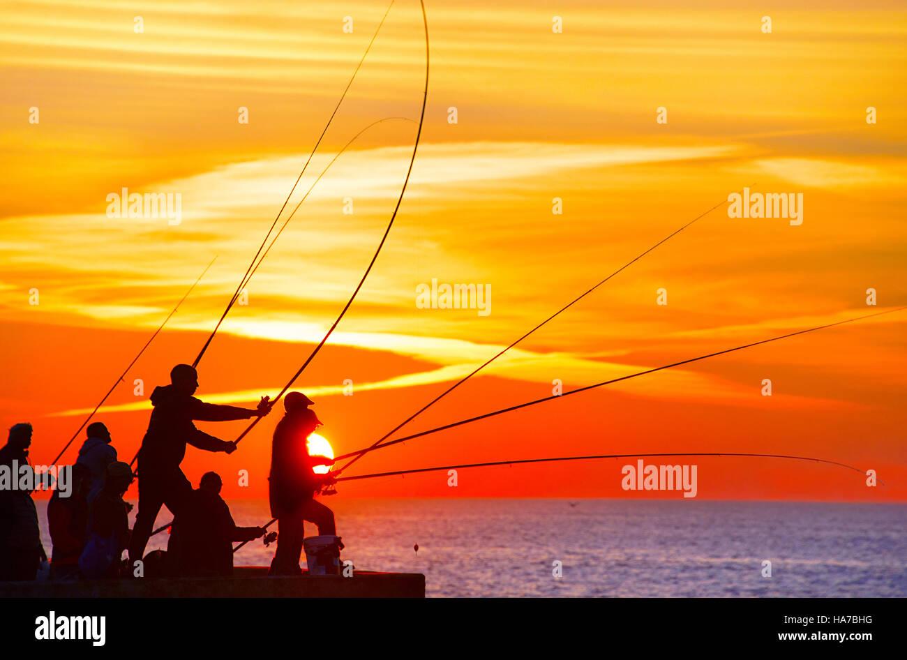 Gruppo di pescatore su un molo al tramonto. Porto, Portogallo Foto Stock