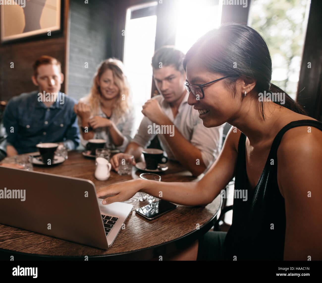 Gruppo di amici in cafe guardare qualcosa online su laptop. Giovani uomini e donne al ristorante guardando il laptop. Immagini Stock