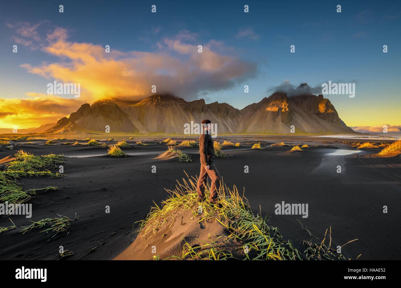 Escursionista godersi il tramonto a Vestrahorn (Batman) di montagna e la sua spiaggia di sabbia nera in Islanda Foto Stock