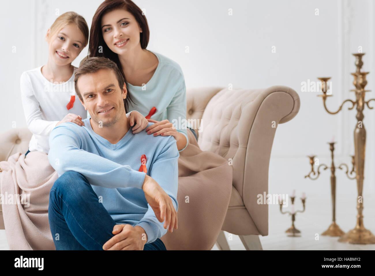 Felice famiglia gioiosa che mostra la loro simpatia per i malati di AIDS Immagini Stock