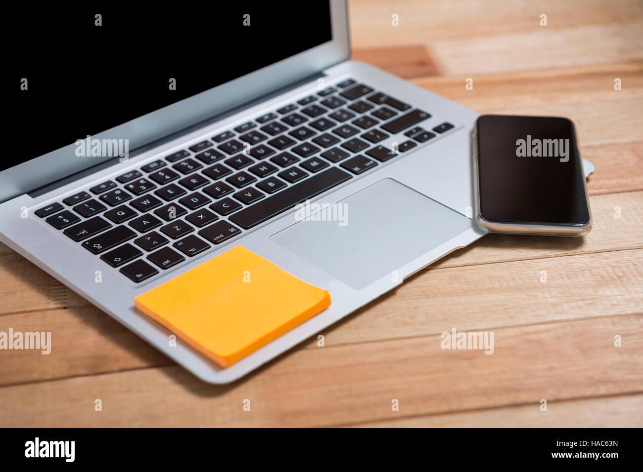 Telefono cellulare e una nota adesiva su laptop Immagini Stock