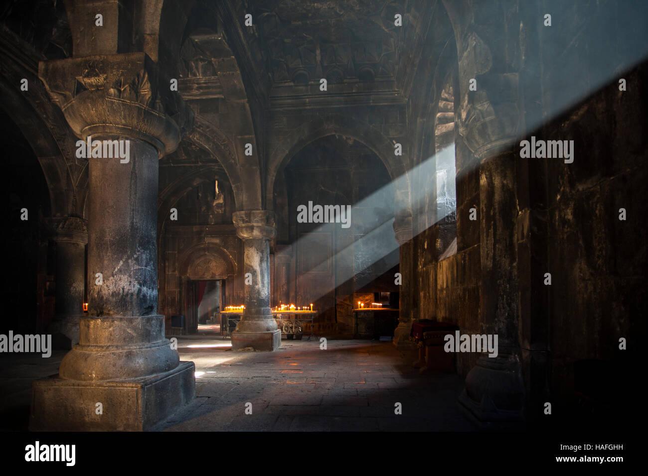 Interno del borgo medievale di Chiesa apostolica armena - Gegard monastero. Numerose le candele e i raggi del sole Immagini Stock