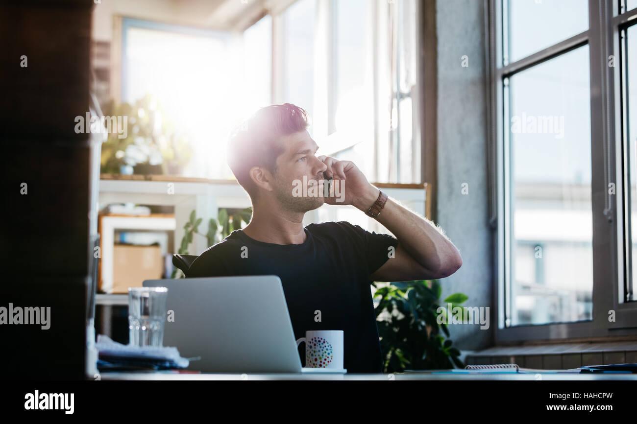 Colpo di giovane uomo seduto al suo ufficio parlando al cellulare. Business man lavorando alla sua scrivania con Immagini Stock