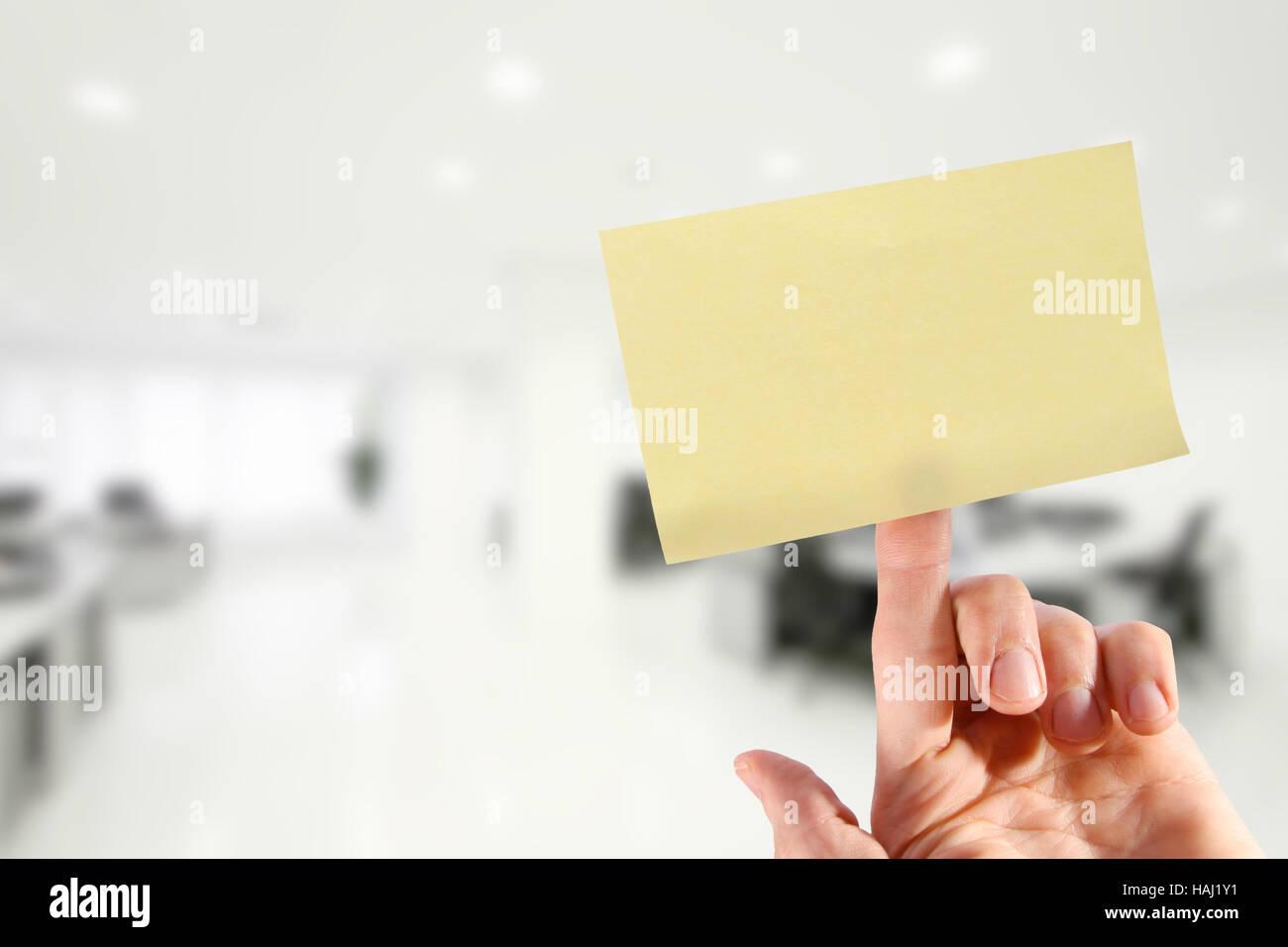 Mano con vuoto nota adesiva sul dito in ufficio Immagini Stock