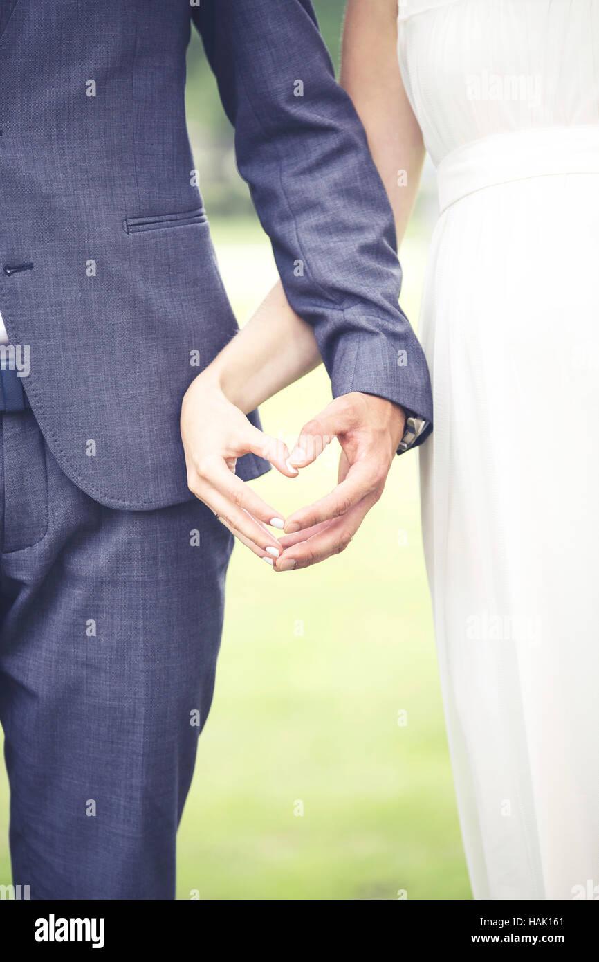 Matrimonio - sposa e il suo fidanzato che mostra il cuore con le mani Immagini Stock