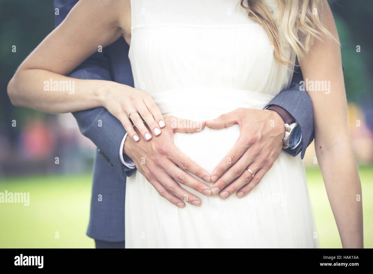 Sposi novelli - a forma di cuore ad mani dell'uomo sulla donna di ventre Immagini Stock