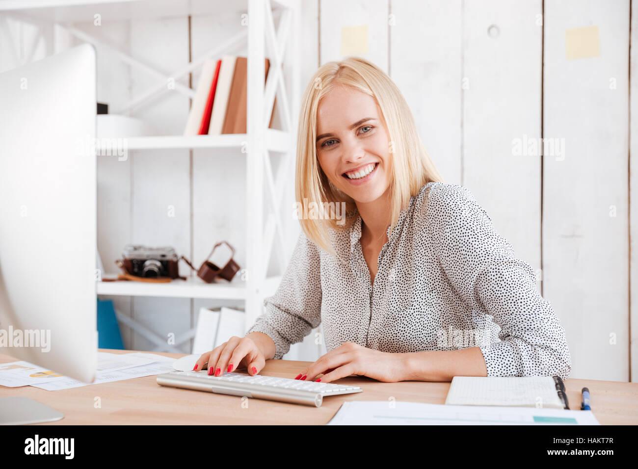 Ritratto di un felice young business donna seduta con il computer in ufficio Immagini Stock