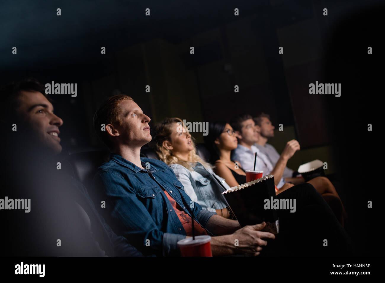 Giovane uomo con gli amici nella sala cinema guardare film. Gruppo di persone che guardano film in teatro. Immagini Stock