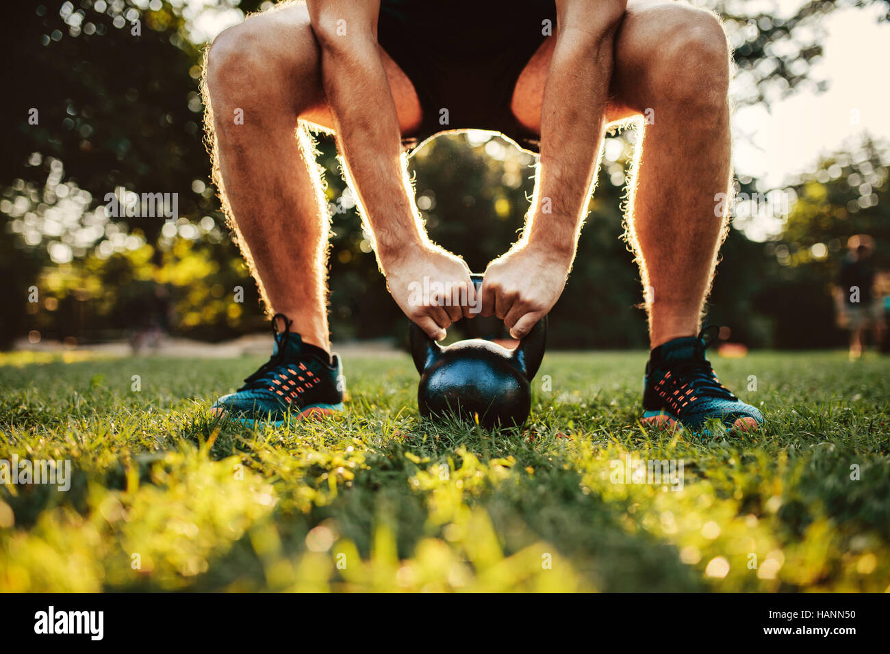 Ritagliato colpo di montare il giovane uomo facendo kettlebell allenamento nel parco, concentrarsi sulle mani bollitore Immagini Stock