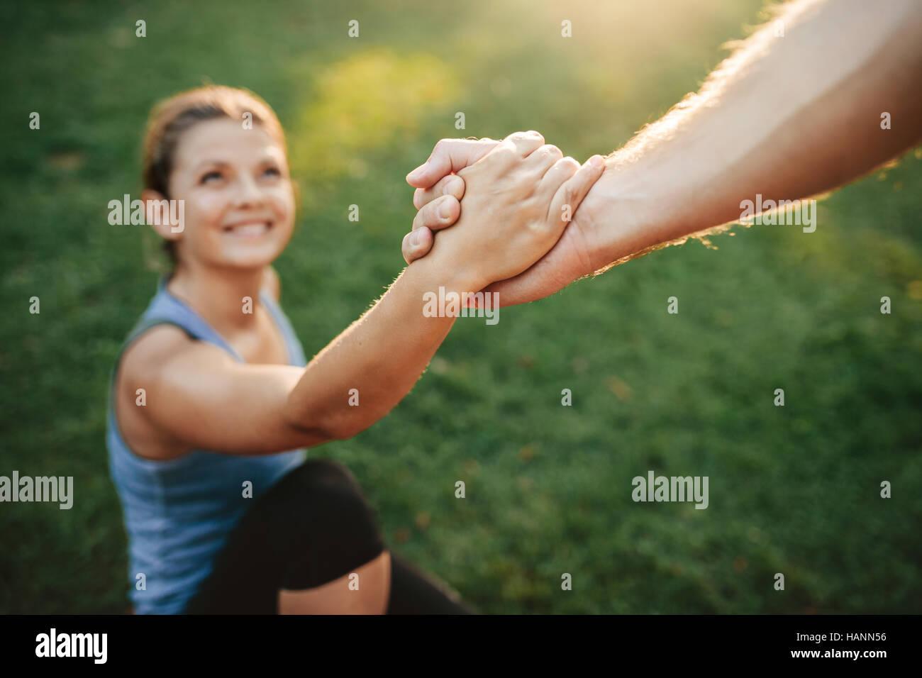 Immagine ravvicinata di uomo donna aiuta ad alzarsi in piedi. Concentrarsi sulle mani del giovane esercitare presso Immagini Stock