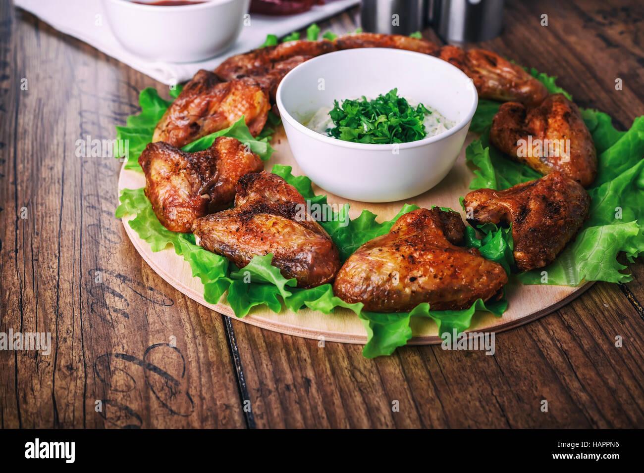 Deliziose grigliate di ali di pollo con aglio e salsa di pomodoro con lattuga su un round di bordo su legno sfondo Immagini Stock