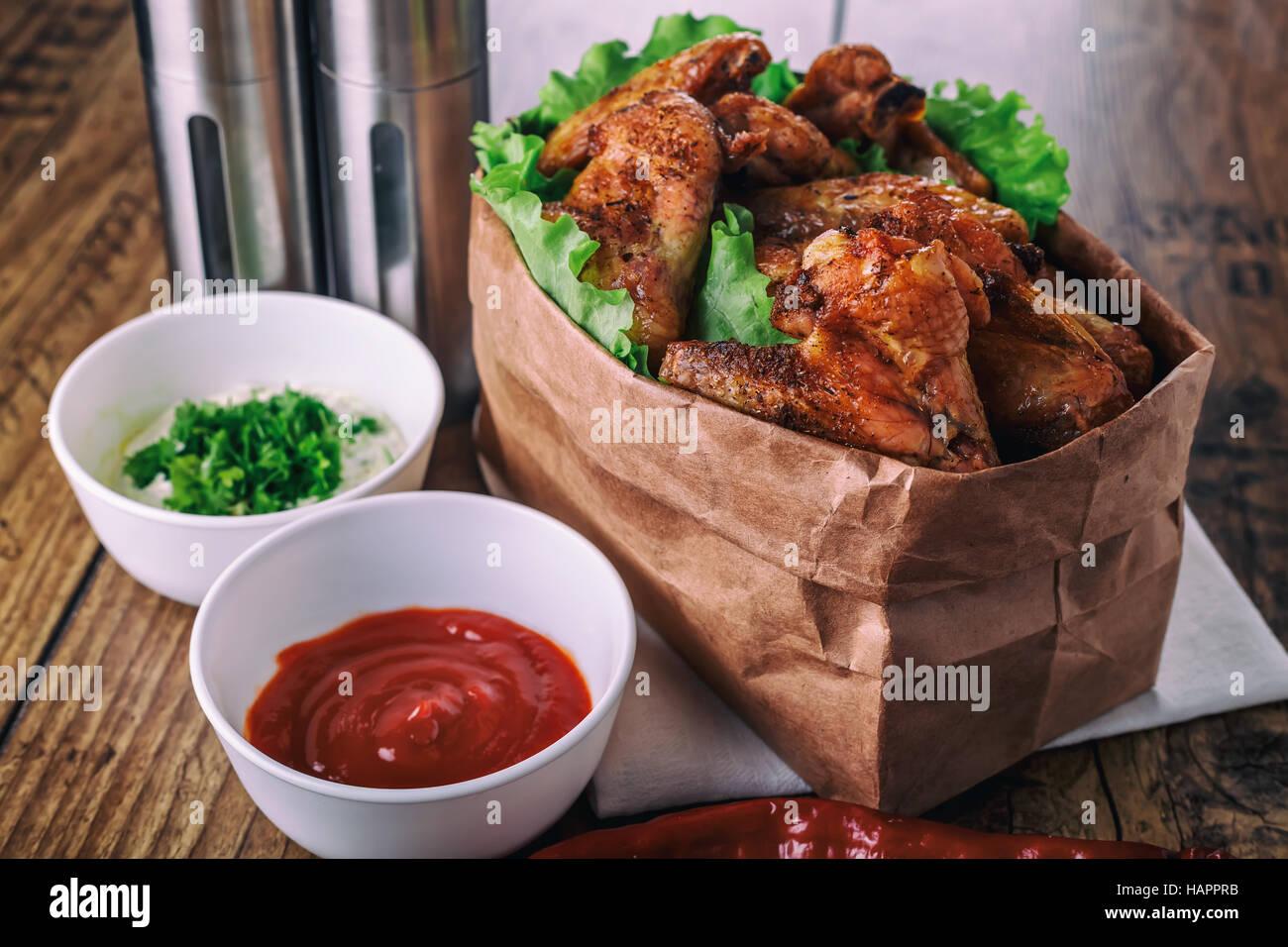 Deliziose grigliate di ali di pollo con aglio e salsa di pomodoro con lattuga in alimenti sacchetto di carta su Immagini Stock