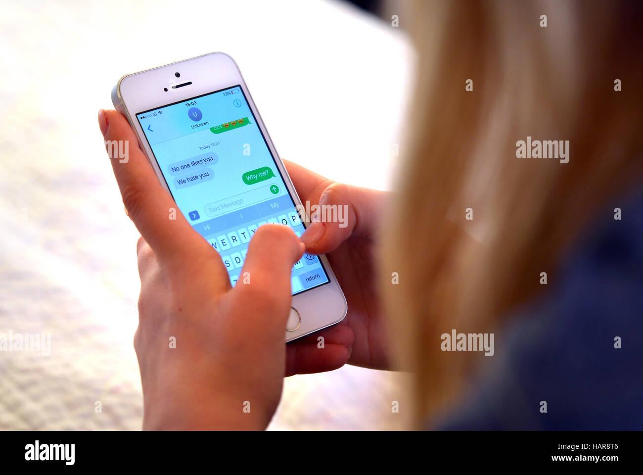 Teen tenendo il telefono cellulare con il bullismo offensiva dei messaggi di testo Immagini Stock
