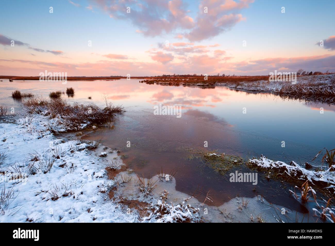 Sunrsie oltre il fiume in inverno Immagini Stock