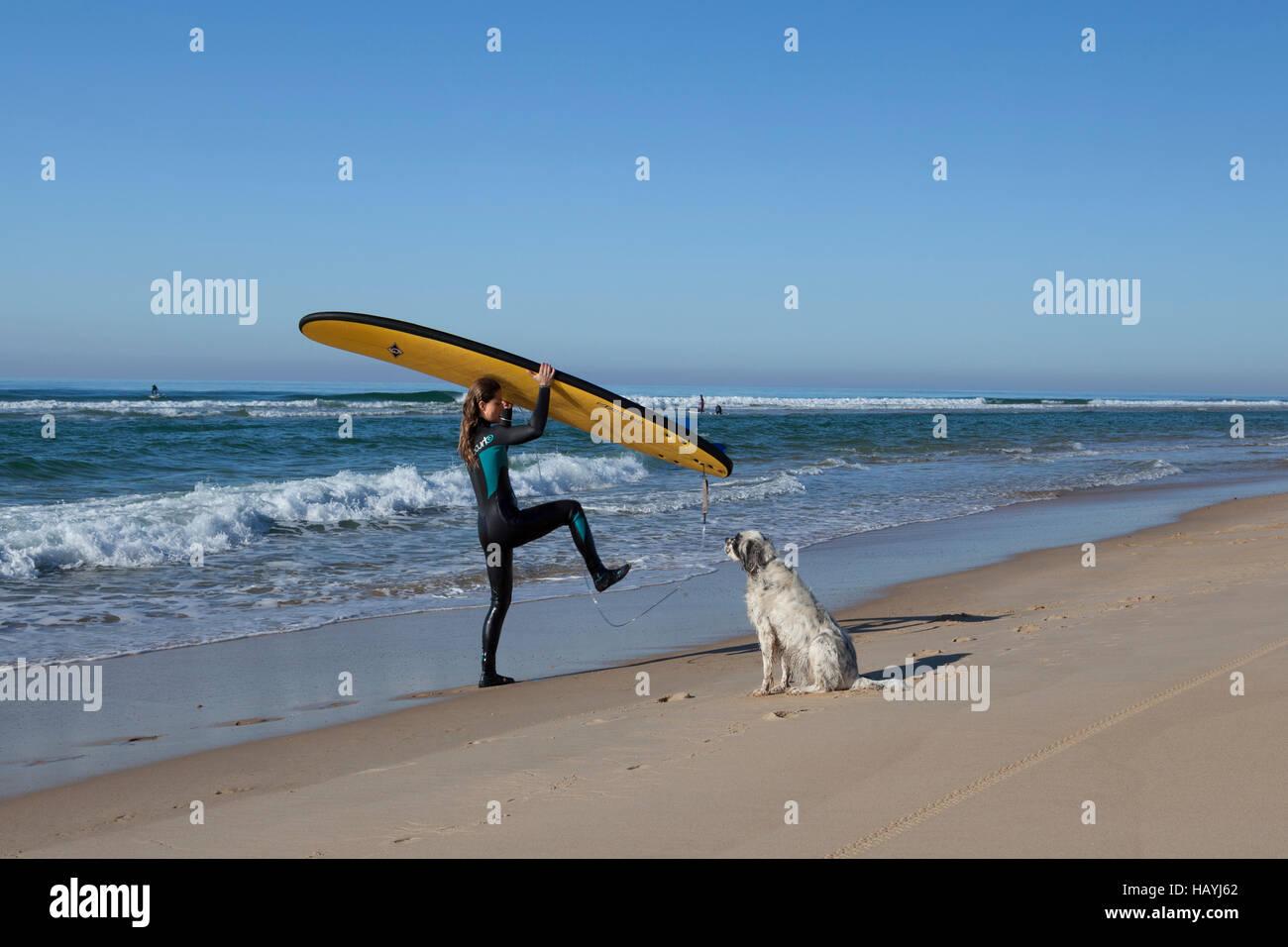 Un surfista femmina in uscita dell'acqua e liberare dal guinzaglio della sua tavola da surf sotto lo sguardo del Foto Stock