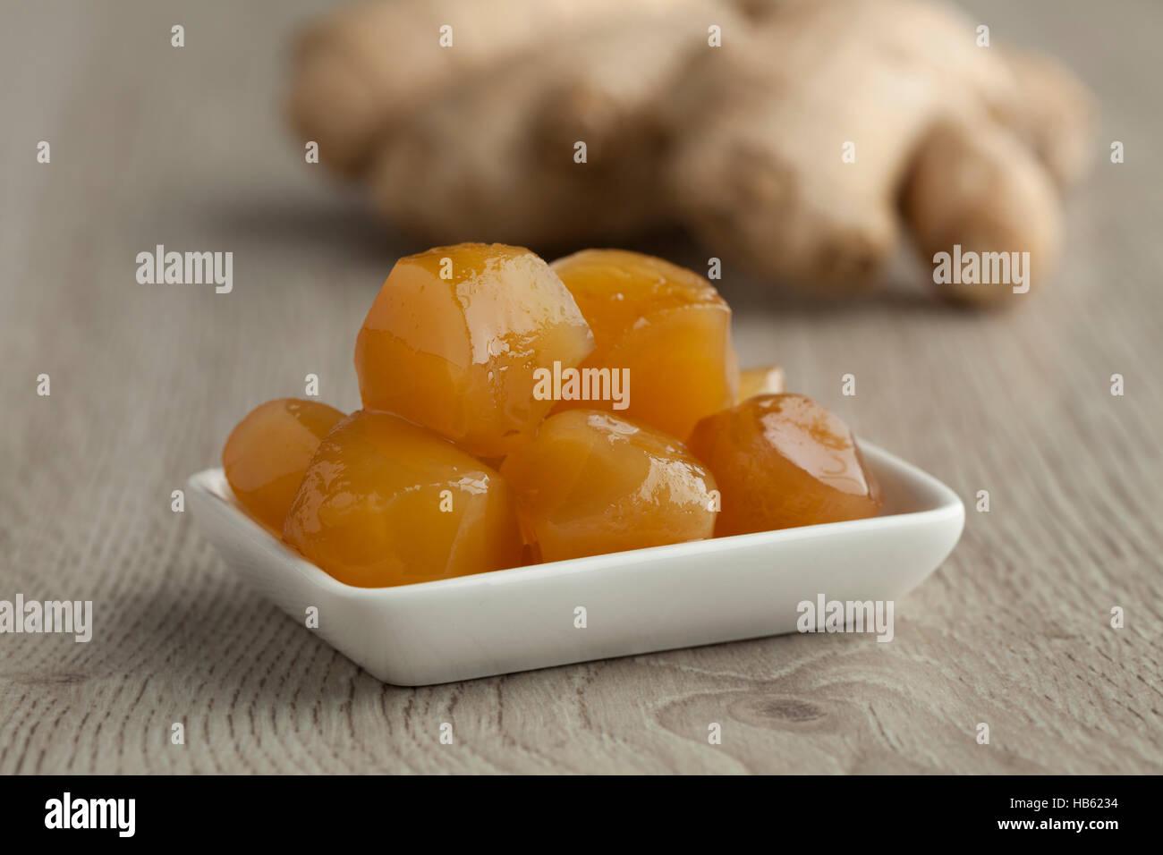 Il piatto con il gambo di zenzero in sciroppo con il gingerroot fresco in background Immagini Stock