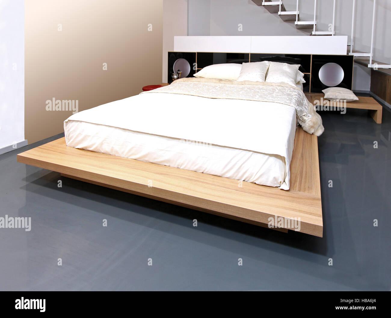 Moderno interiore camera da letto con grande letto in legno Immagini Stock