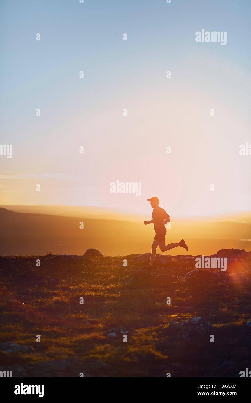 Uomo che corre sulla Scogliera al tramonto, Keimiotunturi, Lapponia, Finlandia Immagini Stock