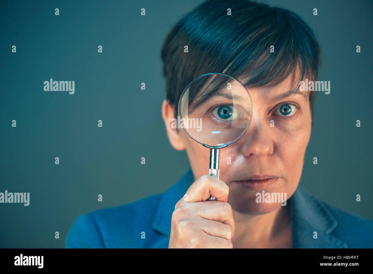 Bella imprenditrice guardando attraverso la lente di ingrandimento - cercare, scoprire, esplorare e indagare e analizzare Immagini Stock